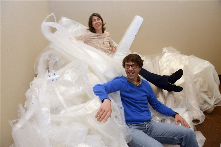 "2baumann1027 Carnegie International co-curator Daniel Baumann and his wife, Gabriella Burkhalter, play in a pile of bubble wrap at the Carnegie Museum of Art. Ms. Burkhalter, an urban planner, is researching the history of playgrounds and is guest curator of ""The Playground Project,"" a component of the current International."