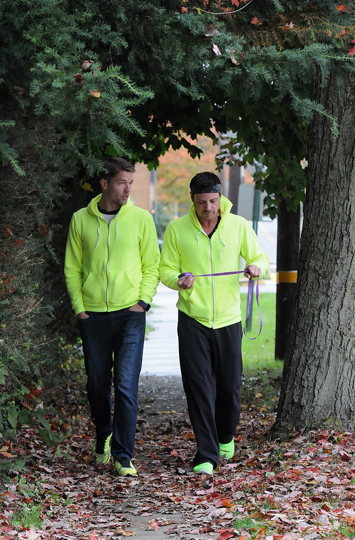 20131023radBullyWalkLocal02-1 Ronnie Kroell, left, and Elliot London walk along Main Street in Prospect, Butler County, Wednesday afternoon. They are walking from Chicago to New York to raise awareness of the problem of bullying. Every mile, they attach a purple ribbon to a sign or tree.