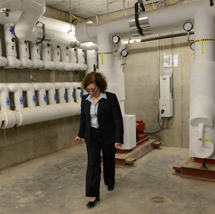 20131024DsLoc06CommunityHou Myrna Zelenitz, executive director of the East End Cooperative Ministry, walks through the geothermal wells in the basement of the new facility.