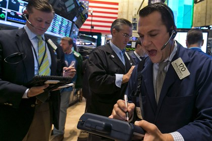 New York Stock Exchange Trader Michael Zicchinolfi, right, works on the floor of the New York Stock Exchange on Friday.