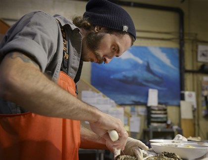 Kyle Houghtelin, Fishmonger Kyle Houghtelin, 27, of North Braddock, shucks oystersat Penn Ave. Fish Company in the Strip District.