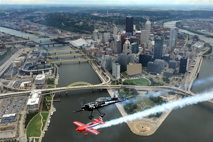 Pilots over Downtown Pittsburgh skyline Pilots Jack Knutson, flying the red Extra 300S aircraft, and Rob Holland, at the controls of an MX2, pass over Downtown Pittsburgh.
