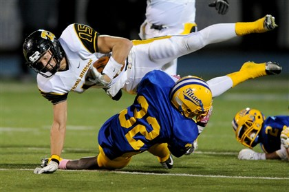 1025mhMifflinVsThomasJeffersonSports05-1 Thomas Jefferson's Chase Winovich dives over West Mifflin's DiAngelo Mitchell last month at Titan Stadium. TJ shutout West Mifflin, 35-0.