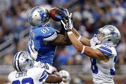 megatron1028-1 Detroit Lions wide receiver Calvin Johnson (81) pulls in a 54-yard reception as Dallas Cowboys cornerback Brandon Carr (39) and Dallas Cowboys defensive back Jeff Heath (38) defends in the fourth quarter of an NFL football game in Detroit, yesterday.