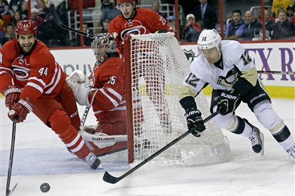102813_penguins01 The Penguins' Chuck Kobasew and the Hurricanes' Jay Harrison reach for the puck as Hurricanes goalie Justin Peters defends the net during the first period.