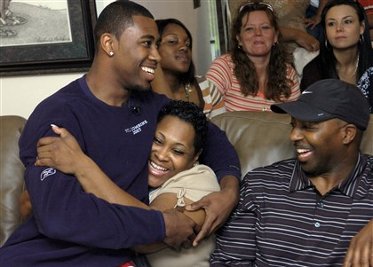 revis1-1 Aliquippa's Darrelle Revis sits on the lap of his mom, Diana Gilbert, and next to his father, Darryl Revis, at his home before he was drafted by the New York Jets in the first round of the 2007 NFL draft.