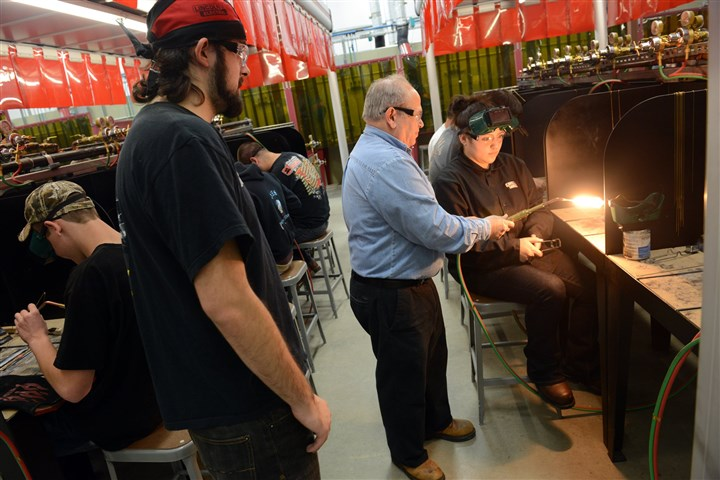 20131101lfPtiBusiness01 John Foley, welding instructor at Pittsburgh Technical Institute, demonstrates how to use a welding torch to A-Lexus Zorn, 18, while Jordan Santiago, 19, looks on at the new energy training center.