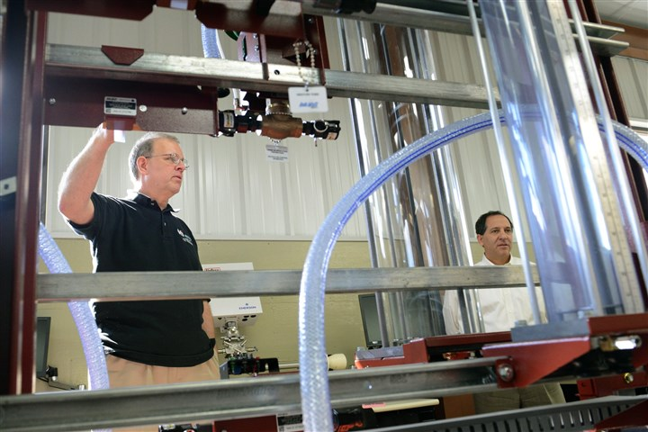 20131101lfPtiBusiness02-1 Dave Becker, left, department chairman of the School of Energy and Electronics Technology at PTI, explains the usage of a liquid flow stimulator to Jim Neville, vice president-Inside Operations of Equipment & Controls, at the PTI new energy training center.