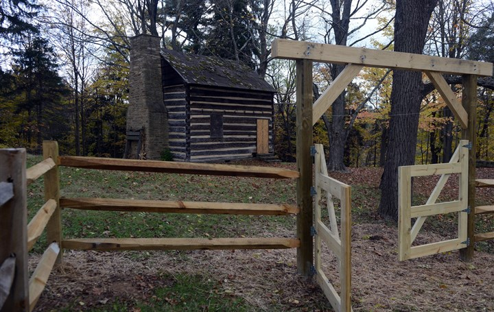 PittsburghBotanicGard.1 A fenced-in apple orchard and log cabin at the Pittsburgh Botanic Garden.