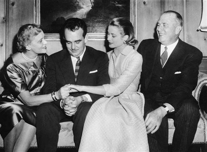 PrincessGrace2 Prince of Monaco has that bridegroom-to-be look as his fiancee, actress Grace Kelly, shows her engagement ring of interlocking diamonds and rubies to her mother, Mrs. Margaret Kelly, during a press interview following announcement that Miss Kelly will marry the prince. Miss Kelly's father John smiles his approval at right.