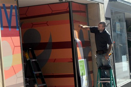 20131102ppWindows1EAST Sam Davis with Sign-A-Rama installs artwork by Seton Hill University students in the second phase of a project to beautify vacant storefronts in Greensburg.