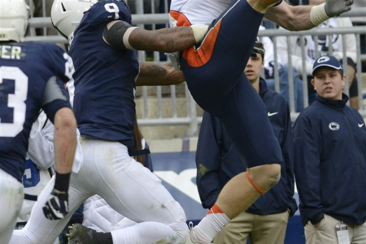 psu1103b-1 Illinois wide receiver Steve Hull, right, catches a pass over Penn State cornerback Jordan Lucas in the second half of a game earlier this month in State College.