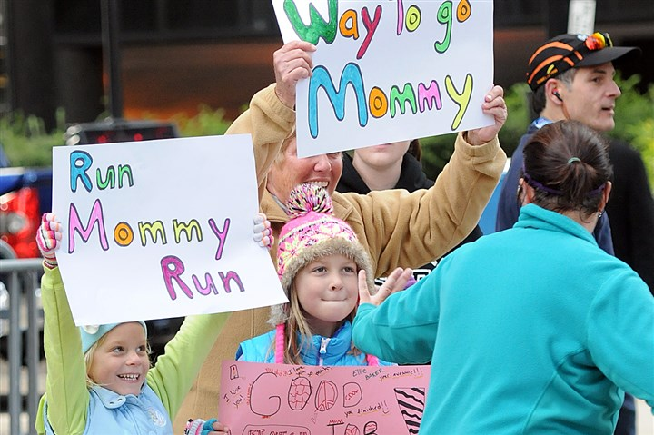 EQT Pittsburgh 10 Miler race supporters Tracie Baker of Cranberry is greeted by her children, Addie, 5, and Ellie, 7, and her mother-in-law Cathy Wagner as she runs along Liberty Ave. to the finish line.