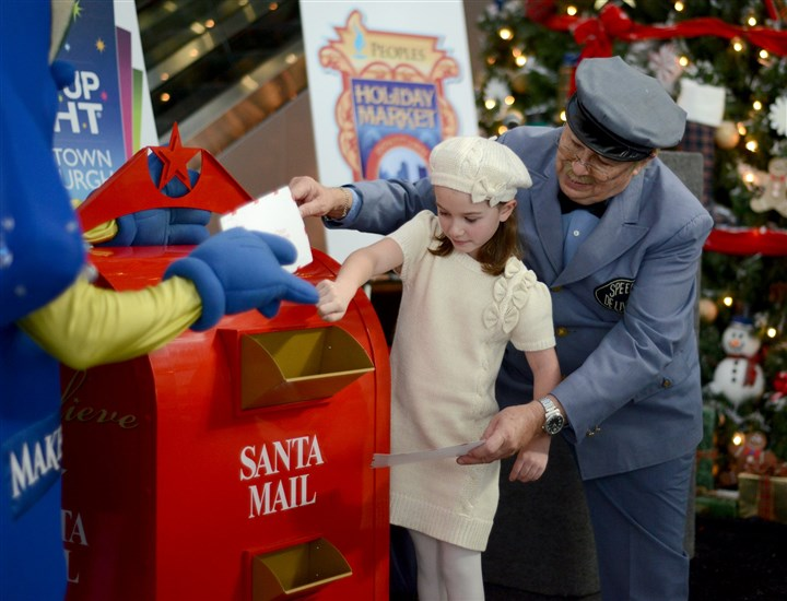"1106mhHolidayAnnouncementLocal02-1 Katie Foley, 8, and Mr. McFeely from ""Mister Rogers' Neighborhood,"" place the first Make-A-Wish letters to Santa Claus into a Santa Mailbox during a press conference Wednesday at One Oxford Centre, Downtown."