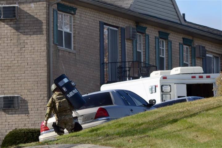 20131106radHempfieldStandoffLocal01 A state police officer in SWAT gear approaches the Hempfield Heights Apartments in Hempfield after two people were found dead in a parking lot there early Wednesday.