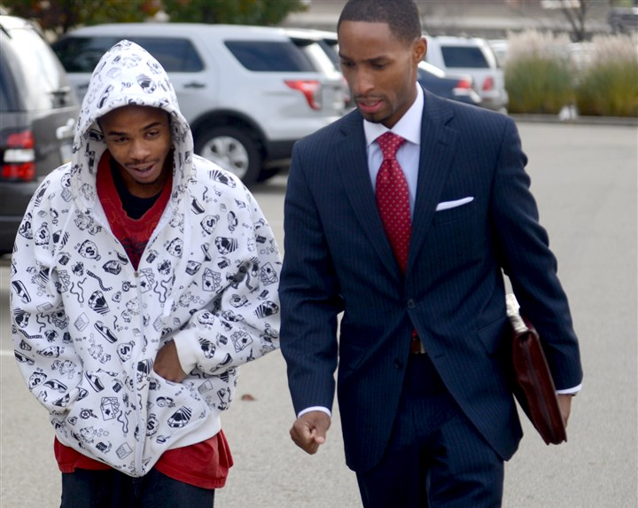 11082013mhBlueSurrendersLocal Jequan Frierson, left, — with his attorney Blaine Jones — enters police headquarters Friday. Mr. Frierson, 20, was charged with homicide, conspiracy and robbery in the Oct. 8 shooting death of 21-year-old Omar Islam.
