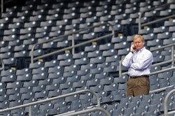 Pirates general manager Neal Huntington makes a call as the team works out at PNC Park in September 2013.