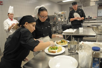 20121109ttLocalCookoff1 At a Great American Chef High School Cookoff at Pittsburgh Technical Institute in North Fayette, Cheyene Edwards, 17, front, a senior at Carlynton High School, and Brandy Peoples, 17, a junior at Quaker Valley High School, put together their entry: duchess potato and pan-fried chicken breast with home-made breadcrumbs, and a vegetable salad medley sauteed on a bed of spinach.