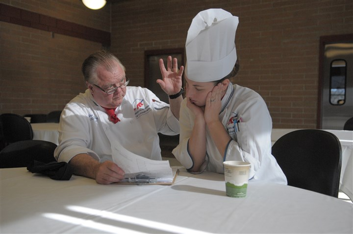 20121109ttLocalCookoff2-1 During the Great American Chef High School Cookoff, Norman Hart and Amanda Flesch, both of the American Academy of Culinary Arts, discuss the rating of one of the teams.