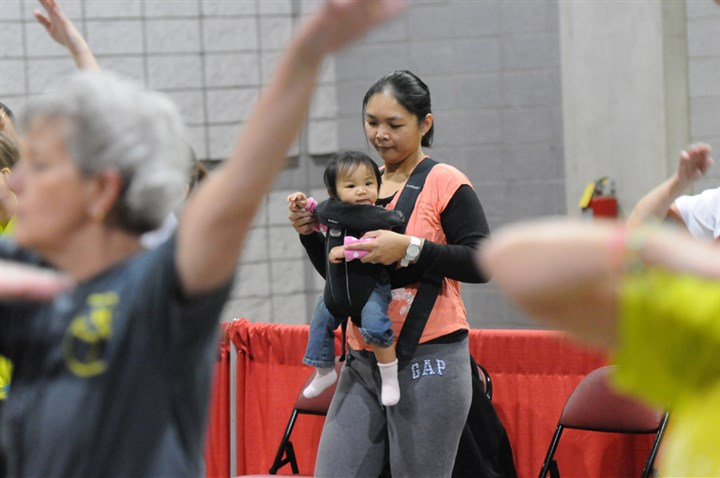 20131109lfDiabetesLocal02-1 Mary Naguit, 33, of Pittsburgh, exercises with her 9-month-old daughter Olivia at the American Diabetes Association Expo in the David Lawrence Convention Center on Saturday.