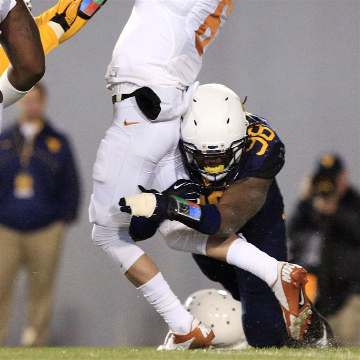wvu1110a Texas quarterback Case McCoy is sacked by West Virginia's Will Clarke during a game in Morgantown, W.Va., on Saturday, Nov. 9, 2013.