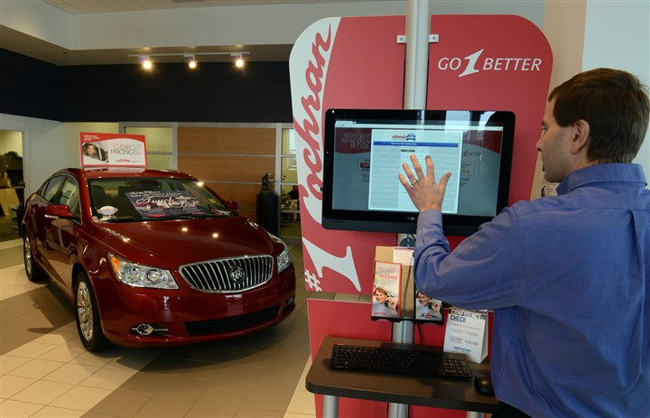 20131113CARBUYINGBiz01 Sales Mmanager John Mann shows comparisions of cars on a kiosk in #1 Cochran's Buick