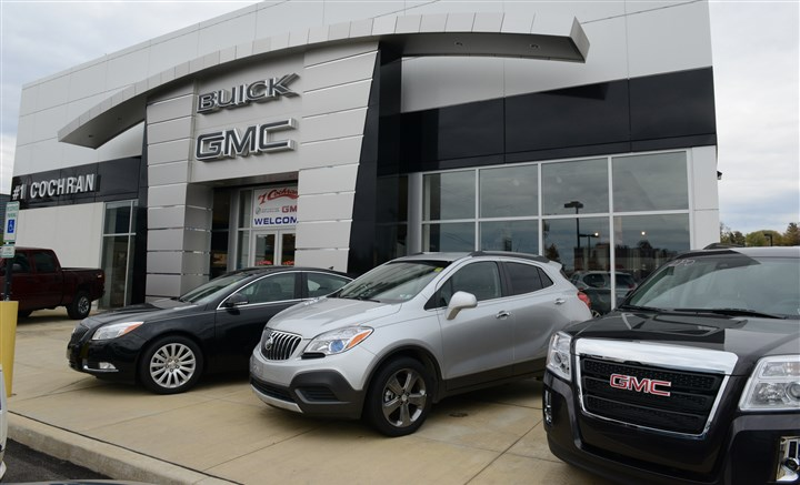 20131113CARBUYINGBiz03-1 GMC showroom in Robinson. Below, vehicles for sale outside the showroom.