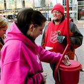 James Love tends Salvation Army red kettle  in Market Square as Kayla Cook, center, and her mother Ellen Collins, left, prepare to make donations.