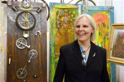 "Kim Cagni of Mt. Lebanon, who has Parkinson's disease, with her painted doors and other artworks for her exhibit ""A Door It!"" last year at Bicycle Heaven in Manchester. She and Dan McCarthy are planning a fundraiser in April at the Hollywood Theater in Dormont."