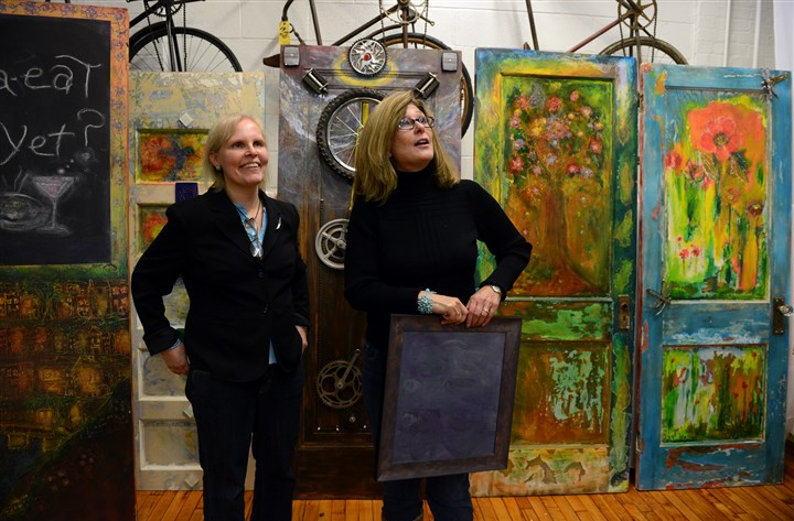 "20131113bwKimLocal01 Kim Cagni of Mt. Lebanon, left, who has Parkinson's disease, works with Linda Kearns of Mt. Lebanon to arrange Ms. Cagni's painted doors and other artwork for her exhibit ""A Door It!"" at Bicycle Heaven."