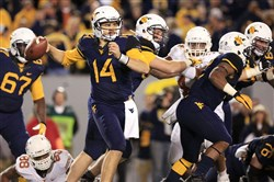 West Virginia quarterback Paul Millard throws to a receiver during a game against Texas in Morgantown, W.Va., on Saturday, Nov. 9, 2013.