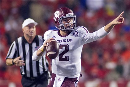 Johnny Manziel In this Sept. 28, 2013, file photo, Texas A&M quarterback Johnny Manziel points as he looks to make a pass during an NCAA college football game against Arkansas in Fayetteville, Ark.