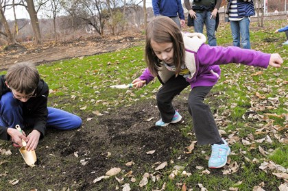 20131116ttParkLocal7-8 After a Saturday groundbreaking ceremony at Aspinwall Riverfront Park, Nathan Vandemark, 13, and Nora Kelley, 6, both of Aspinwall, help to plant bulbs.