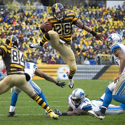 20131117pdSteelersSports01.jpg Le'Veon Bell leaps over top of the Lions' Willie Young in the second quarter for a first down at Heinz Field.