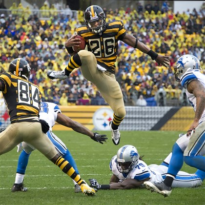 20131117pdSteelersSports01.jpg The Steelers' Le'Veon Bell leaps over top of the Lions' Willie Young for a first down in the second quarter Sunday at Heinz Field.