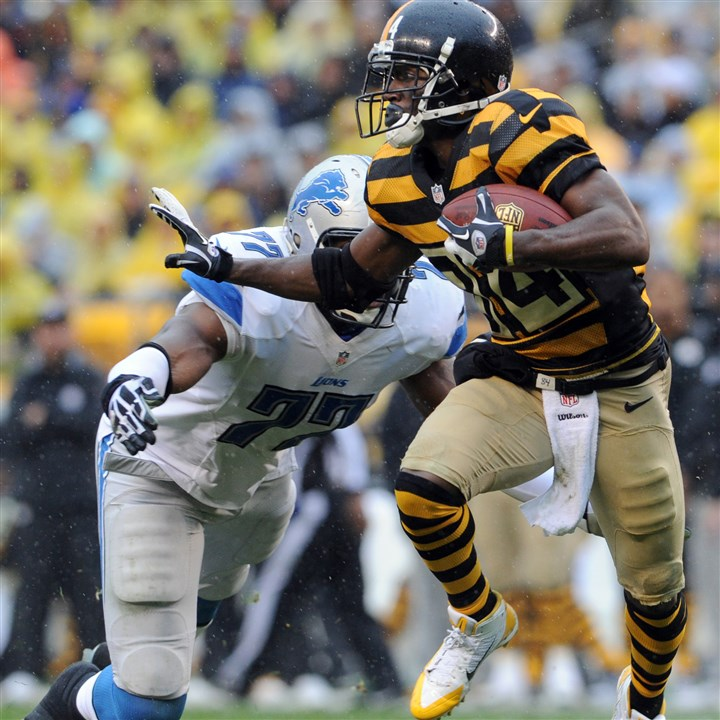 20131117mfsteelers05-2 The Steelers' Antonio Brown carries as he's defended by the Lions' Israel Idonije in the second quarter at Heinz Field Sunday afternoon.
