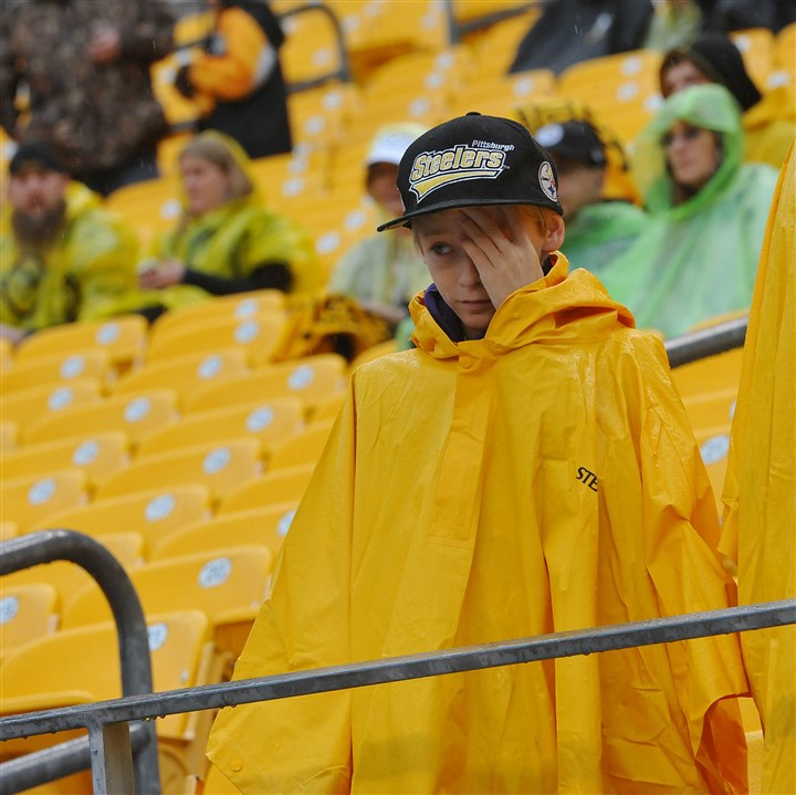 20131117lrsteelerslions01 Joshua Ayers, whose family drove up from Knoxville, Tenn., to see the Steelers-Lions game at Heinz Field, wipes rain out of his eyes before the start of the game.