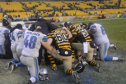 20131117lrsteelerslions30-2 Members of the Detroit Lions and Pittsburgh Steelers kneel in the grass in Heinz Field for a prayer after their game last Sunday.