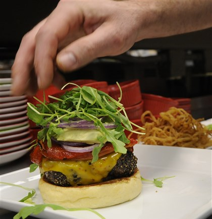 burgatorymag10-7 A finishing touch: adding arugula to a growing burger.
