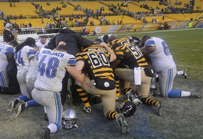 20131117lrsteelerslions30-2 Members of the Detroit Lions and Pittsburgh Steelers kneel in the grass in Heinz Field for a prayer following their Sunday game.