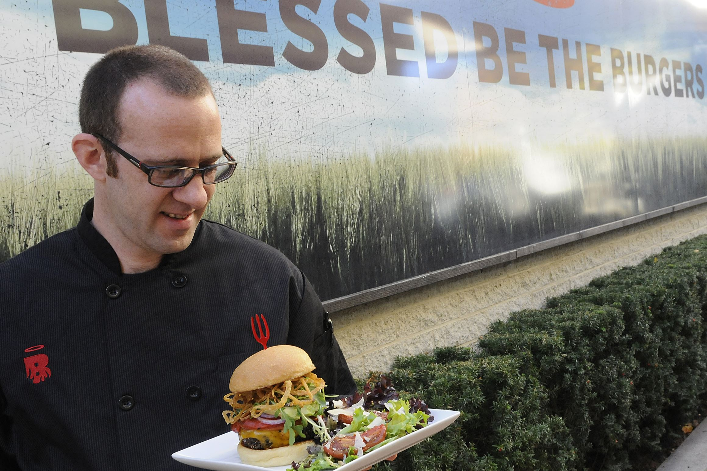 "20131118lrburgatorymag03-1 Brad Kohut , executive chef of Burgatory, beholds a burger with salad. ""Blessed Be The Burgers"" is the local chain's slogan."