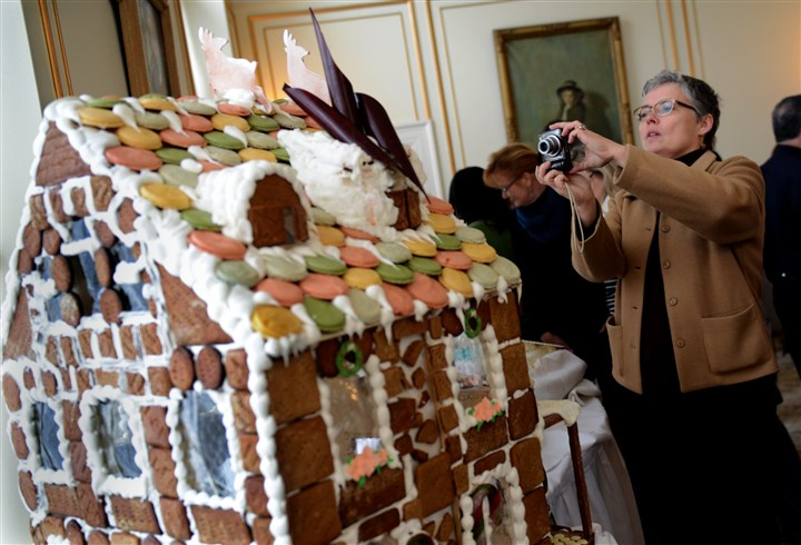 20131119ppToysfortotsLOCAL Deborah Lange of Point Breeze takes photos of a gingerbread house during the kick-off of the ninth annual Toys for Tots drive by Carnegie Mellon University's engineering students and university police.