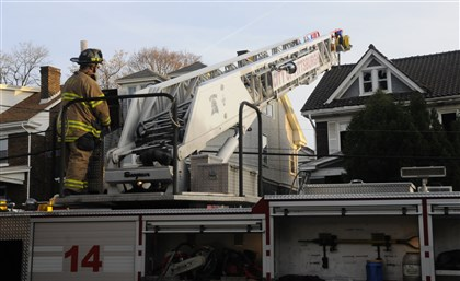 20131120lrbeaconfirelocal01 The aerial ladder is pulled away from 5512 Beacon Street after firefighters battled a three-alarm blaze at the Squirrel Hill home this afternoon.