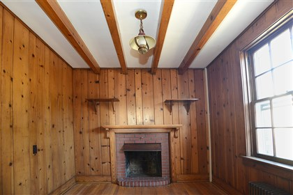 20131120radCenterHomeSunMag.12-2 The den has wood paneling, wood beams and a red-brick gas fireplace.