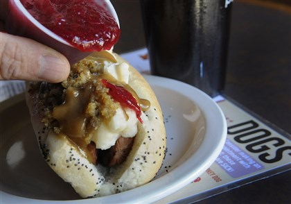 20131120lrturkeydogfood02-1 Thanksgiving hot dog at D's Six Pack and Dogs in Regent Square sits on a plate as cranberry sauce topping is added. It is a turkey sausage with mashed potatoes , corn, stuffing and gravy on a poppy-seed bun.