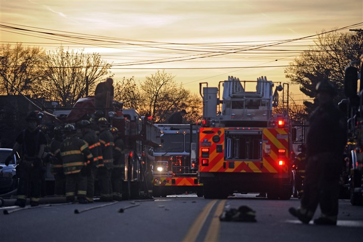 1120mhSquirrelHillFire08-7 The sun sets over Beacon Street in Squirrel Hill while firefighters and rescue workers pack up their vehicles after putting out a three-alarm fire at a home Wednesday evening.