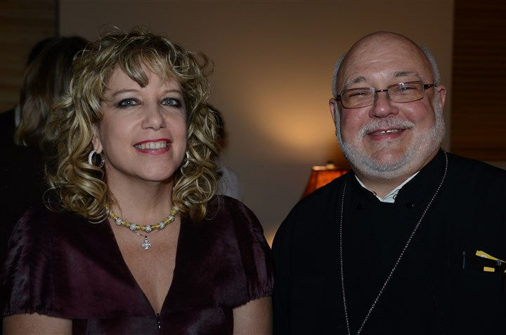 20131121bwFocusSeen04-3 Cynthia Raftis with Fr. Chris Bender.