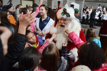 20131122MWHlightupLocal01 A group of fourth- and fifth-graders from Pittsburgh Spring Hill tug on Santa Claus' beard at a lunchtime tree-lighting ceremony Friday at the City-County Building, Downtown.
