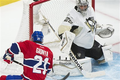 Penguins Canadiens Hockey Penguins goaltender Marc-Andre Fleury keeps an eye on the play as Canadiens right winger Brian Gionta moves in on the net during first-period action.