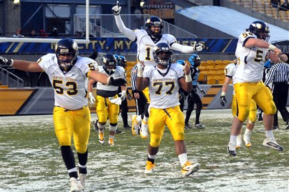 central11241 Central Catholic 's Terrence Stanton (53), Erin McAllister (77) and Dan O'Neill run off the field celebrating after beating Woodland Hills for the WPIAL AAAA football championship.